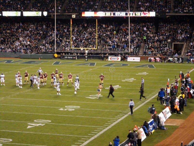 Den nakna manstreakeren kör på fotbollfält i mitt av leken som arkivfoto