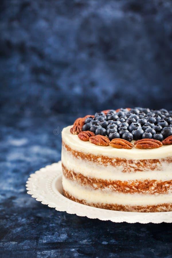 Den nakna morotkakan dekorerade med det nya blåbäret och pecannöten royaltyfri fotografi