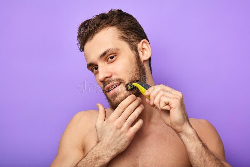 Den nakna muskulösa mannen står med rakkniven i hand, medan raka arkivfoton