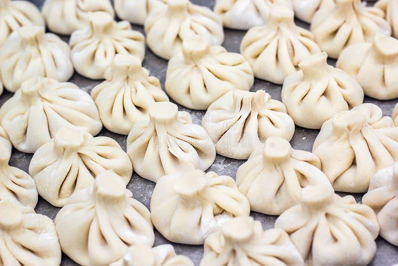 Den nationella georgiska kocken för bakgrund för kokkonstKhinkali metall förbereder gatan fo för maträtten för deg för rått kött  royaltyfri foto