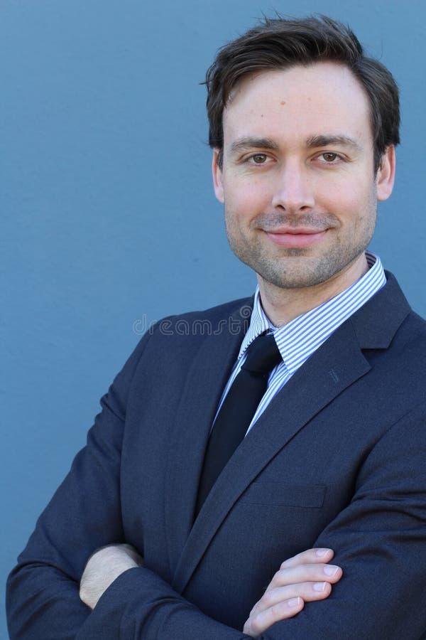 Den naturliga bra seende unga affärsmannen som ler med armar, korsade över blå bakgrund royaltyfria foton