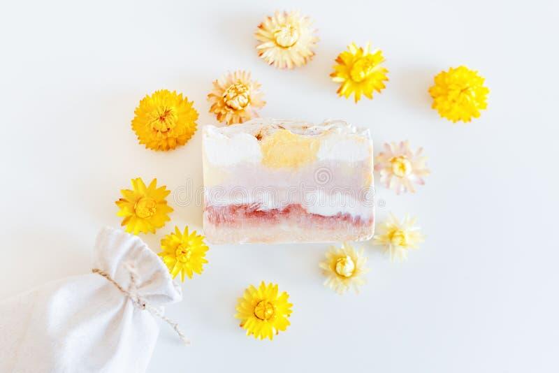 Den naturliga handen - gjorde tvål med torra gula blommor på ljus bakgrundsbrunnsortinställning arkivbild