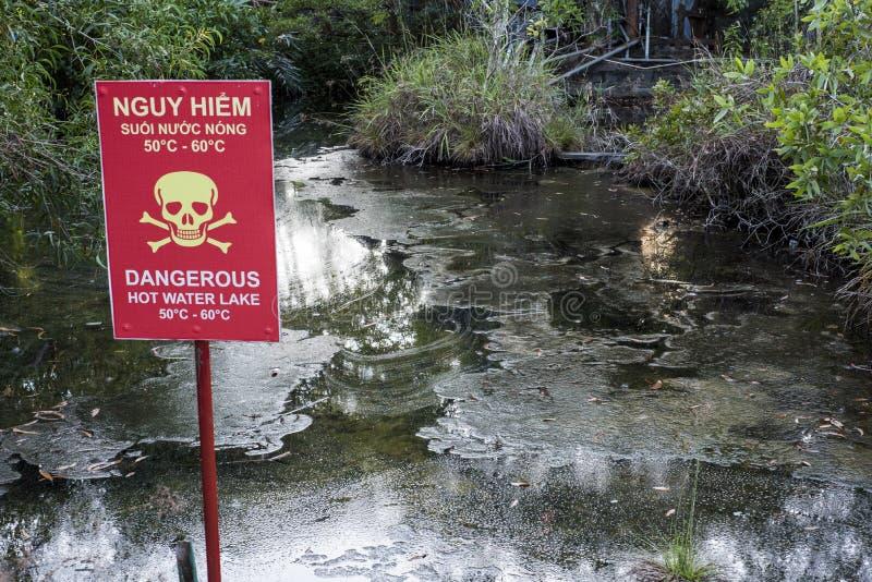 Den naturliga Hot Springs floden och en tvåspråkig engelsk vietnamesisk varning undertecknar i Bình Chau, Vietnam arkivbilder