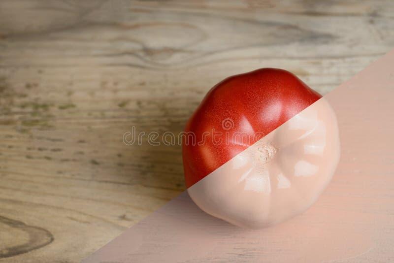 Den naturliga röd och beiga- eller ecruhalvan målade tomaten på träbakgrund royaltyfria bilder
