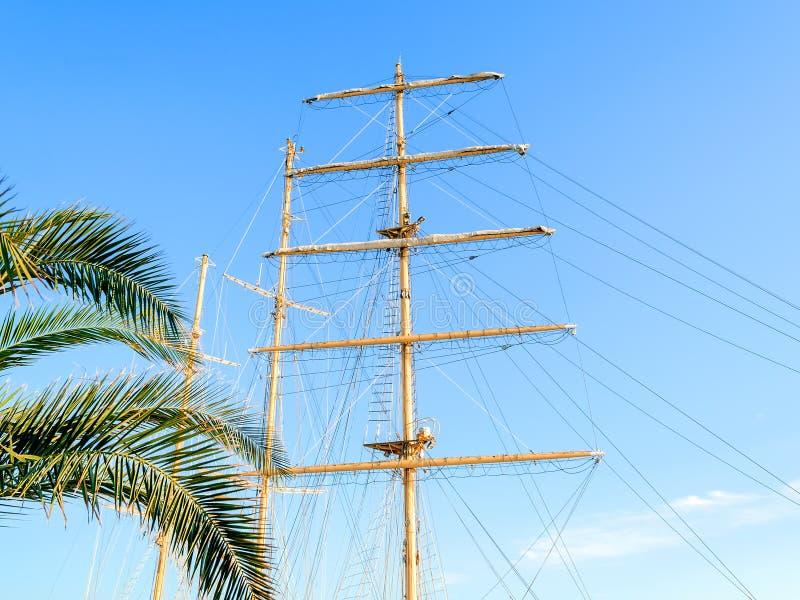 Den nedersta sikten av masten, seglar gårdar med fälld ned seglar och riggning av ett segla skepp mot en blå himmel arkivbild