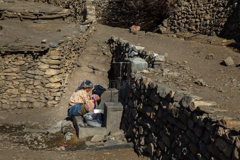Den nepalesiska kvinnan tvättar kläder royaltyfri foto