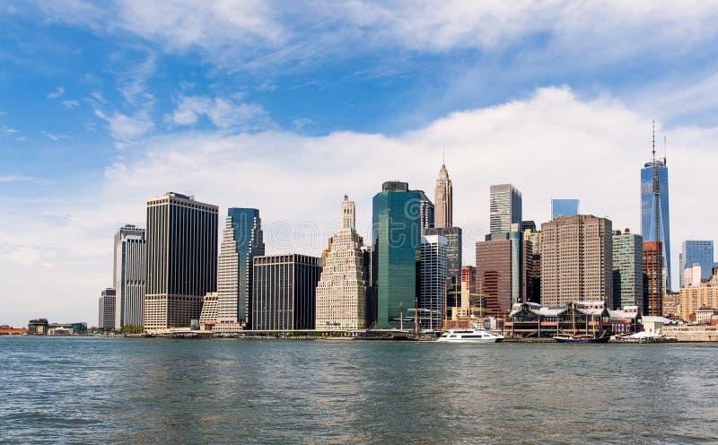 Den New York horisonten och Eastet River under den blåa himlen arkivbild