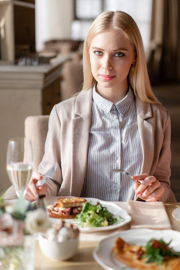 Den Nice kvinnan äter frukosten i kafé Stående av ungt charmigt kvinnligt dricka kaffe och den rostade smörgåsen i modernt royaltyfria bilder