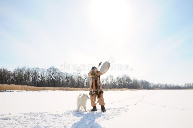 Den nordliga medicinmannen slår tamburin som utför appeller för en ritual, fjädrar Husky hundkapplöpning för ligganderussia för 3 arkivfoto