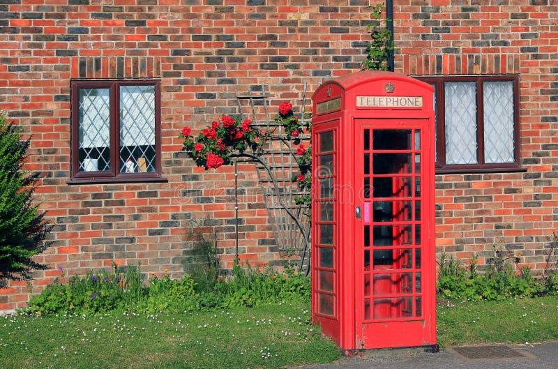 Den nostalgiska telefonasken av väggen för röd tegelsten med vandraren steg framme royaltyfri foto
