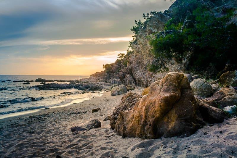 Den Notos stranden med vaggar i den Thassos ön under solnedgång arkivbilder