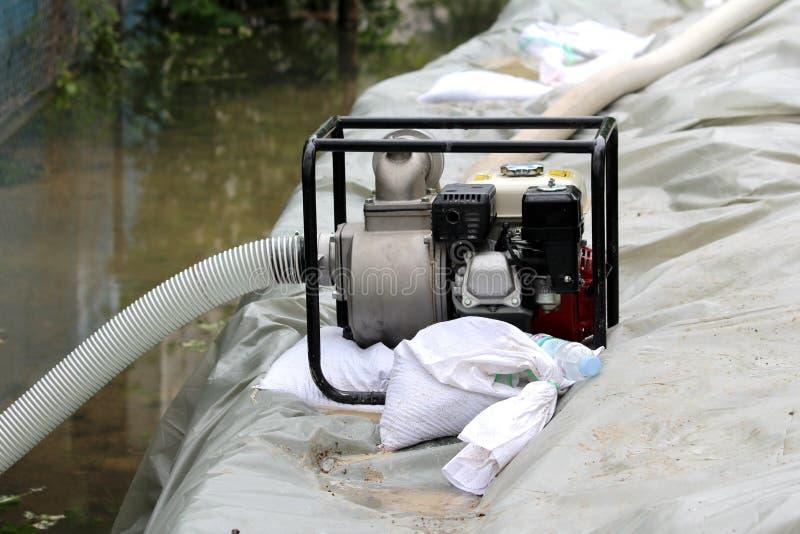 Den nya bensinvattenpumpen med den starka metallramen l?mnade p? sida av den improviserade v?ggen f?r sands?ckflodskydd f?r att p royaltyfria bilder