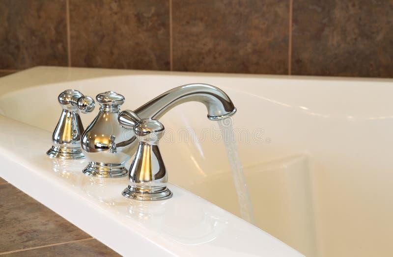 Den nya Chrome vattenkranen i ledar- bad badar royaltyfri bild