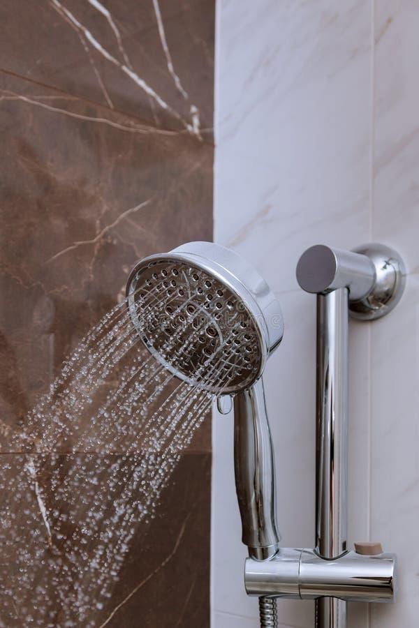 Den nya duschen med vatten tappar att plaska Bevattna spring fr?n den duschhuvudet och vattenkranen i modernt badrum royaltyfria bilder