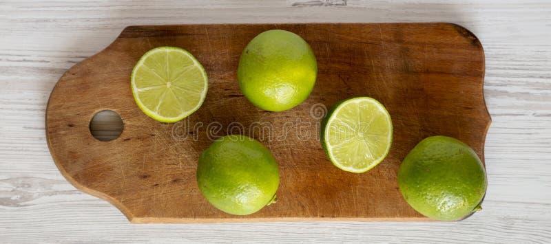 Den nya gr?na citruns kalkar p? ett lantligt tr?br?de ?ver vit tr?yttersida, b?sta sikt Lekmanna- l?genhet, ?ver huvudet, fr?n ?v arkivfoto