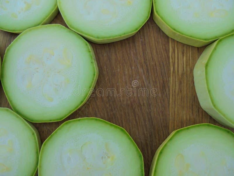 Den nya gröna zucchinin skivade fodrat på en träyttersida royaltyfria bilder