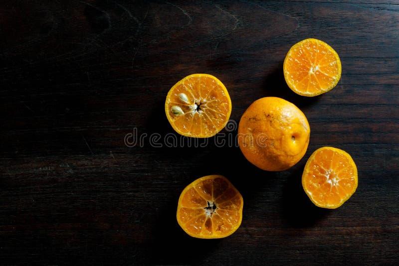 Den nya halvan klippte apelsiner på den mörka trätabellen royaltyfri foto