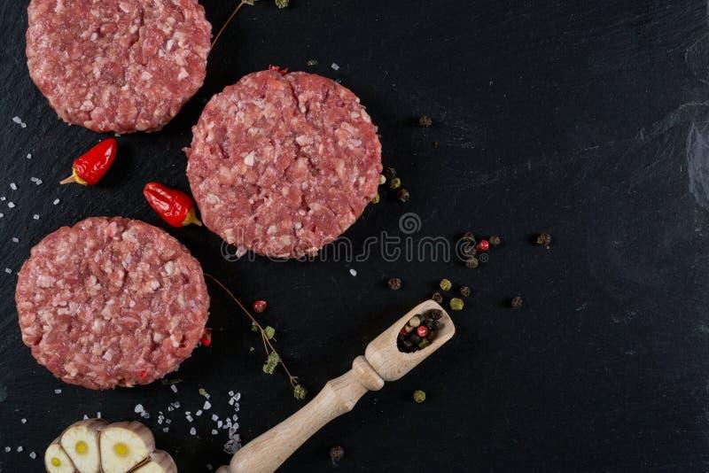 Den nya hamburgarekotletten för rått kött på svarten kritiserar brädet med örter och kryddor för bakgrund royaltyfri foto