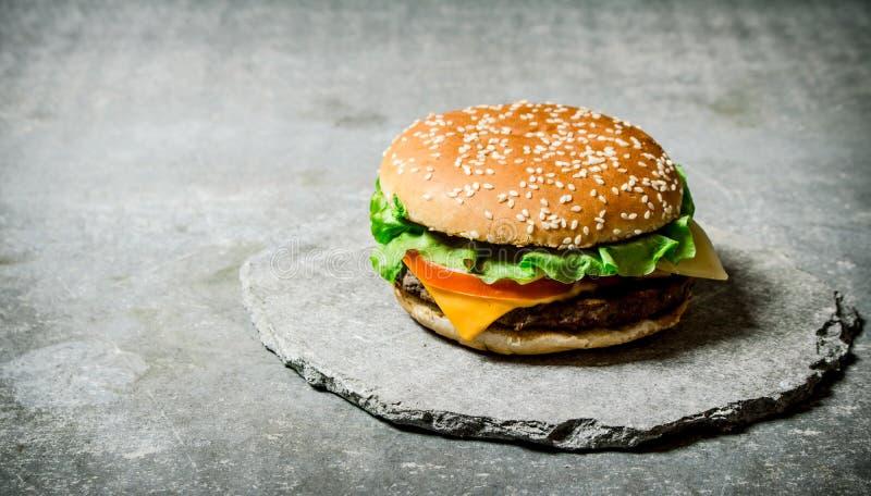 Den nya hamburgaren med ost och kött på en sten står arkivbilder