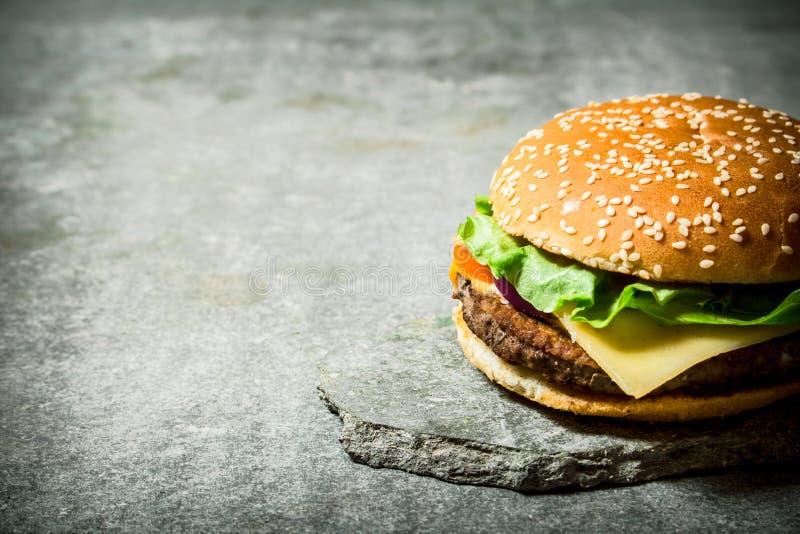 Den nya hamburgaren med ost och kött på en sten står royaltyfri foto
