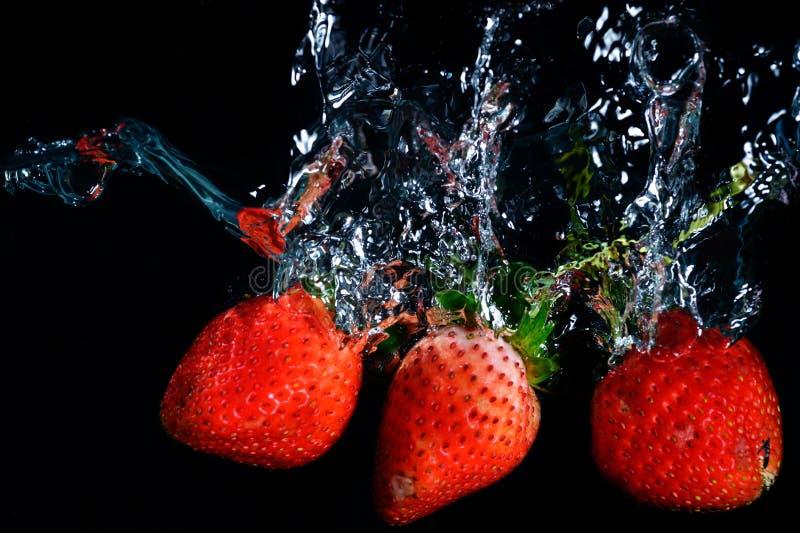 Den nya jordgubben tappade in i vatten med färgstänk på svart backgro arkivfoton