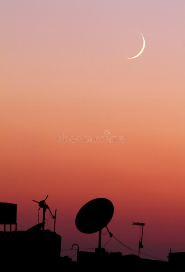 Den nya månen under solnedgång arkivbilder