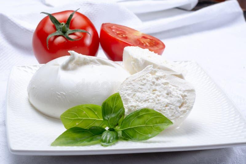 Den nya mjuka vita burrataen, klumpa ihop sig buttery ost som göras från en blandningnolla arkivbilder
