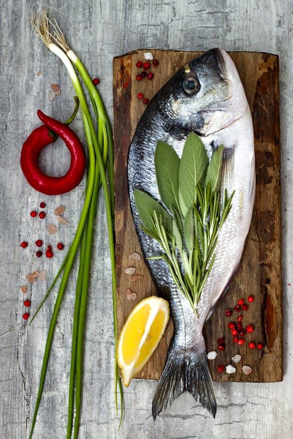 Den nya okokta dorado- eller havsbraxenfisken med citronen, aromatiska örter, grönsaker och kryddor över grå färger stenar bakgru arkivfoton