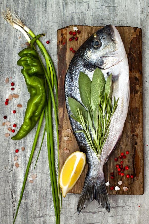 Den nya okokta dorado- eller havsbraxenfisken med citronen, aromatiska örter, grönsaker och kryddor över grå färger stenar bakgru arkivbilder