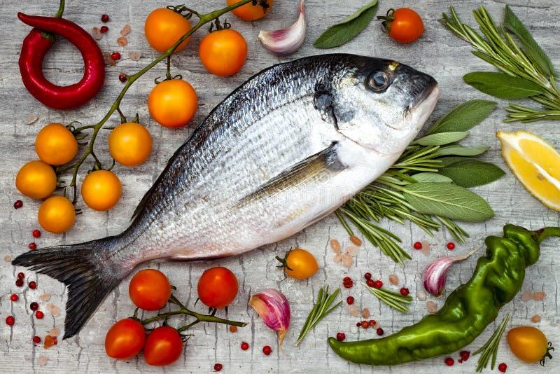 Den nya okokta dorado- eller havsbraxenfisken med citronen, aromatiska örter, grönsaker och kryddor över grå färger stenar bakgru royaltyfria foton