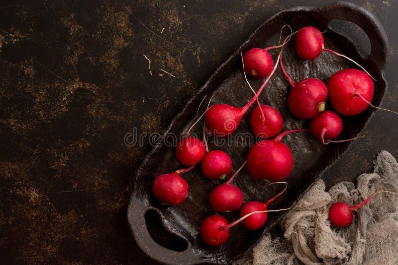 Den nya rädisan spridde på en keramisk lantlig maträtt, mörk bakgrund Bästa sikt, kopieringsutrymme royaltyfri fotografi