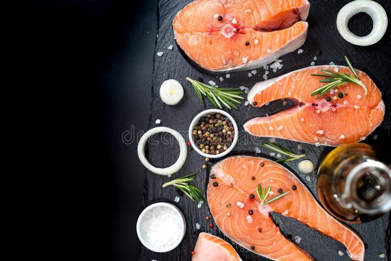 Den nya rå improviserade fisklaxen eller forellen, biffar, i en kastrull för att laga mat, med salt, pepprar på den svarta stenbe royaltyfri bild
