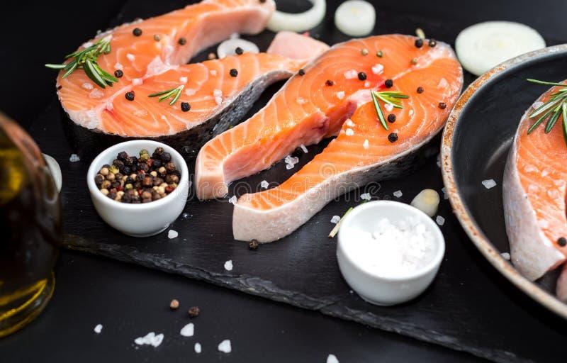 Den nya rå improviserade fisklaxen eller forellen, biffar, i en kastrull för att laga mat, med salt, pepprar på den svarta stenbe fotografering för bildbyråer
