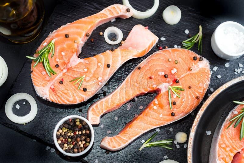Den nya rå improviserade fisklaxen eller forellen, biffar, i en kastrull för att laga mat, med salt, pepprar på den svarta stenbe arkivfoton