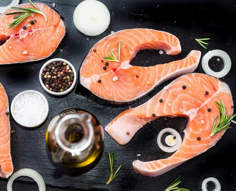 Den nya rå improviserade fisklaxen eller forellen, biffar, i en kastrull för att laga mat, med salt, pepprar på den svarta stenbe royaltyfri foto