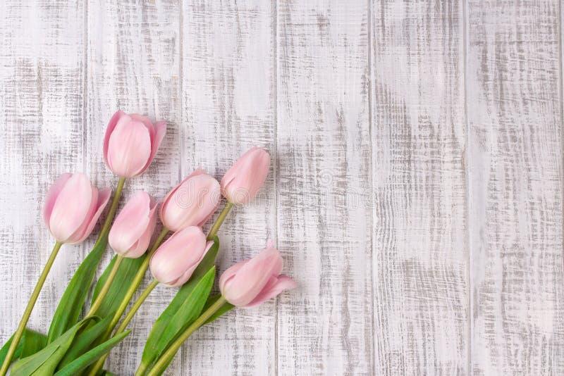 Den nya rosa tulpan blommar buketten på den vita trälantliga tabellen arkivfoto