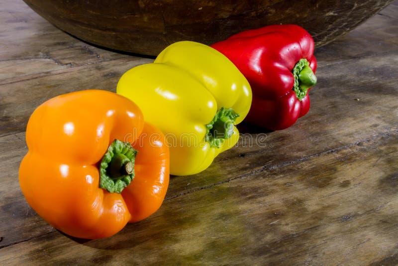 Den nya skörden av söt peppar som är röd, apelsin, gulnar på en trätabell royaltyfri foto