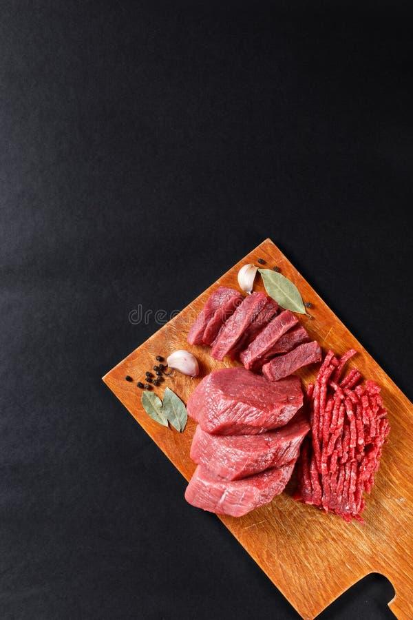 Den nya slaktaren klippte köttsortimentet på svart bakgrund arkivfoton