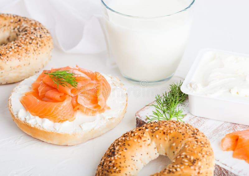 Den nya sunda bagelsmörgåsen med laxen, ricotta och exponeringsglas av mjölkar på ljus köksbordbakgrund banta sund mat royaltyfria foton