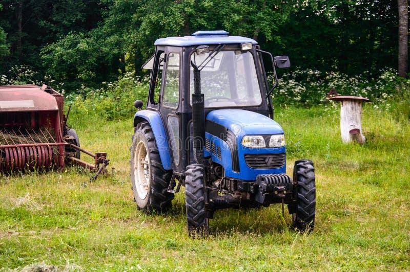 Den nya traktoren med krattar hö arkivfoton
