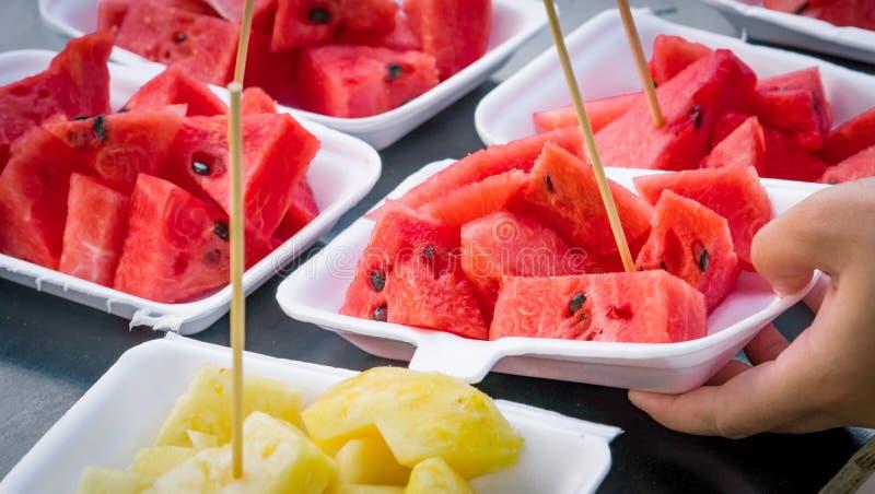 Den nya vattenmelon- och ananasskivan i vitt skum pläterar behållaren på den svarta trätabellen royaltyfri foto