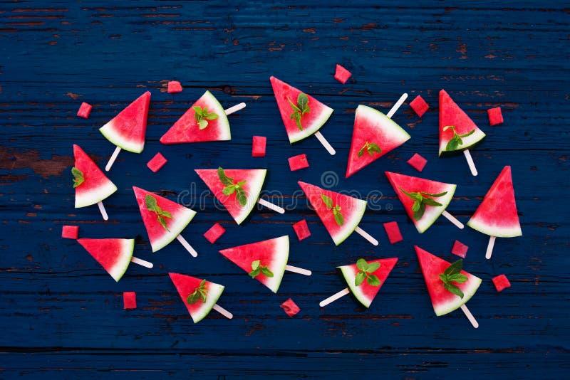 Den nya vattenmelon skivade isglassar på blå lantlig träbakgrund Lekmanna- lägenhet tropisk begreppssommar royaltyfria foton