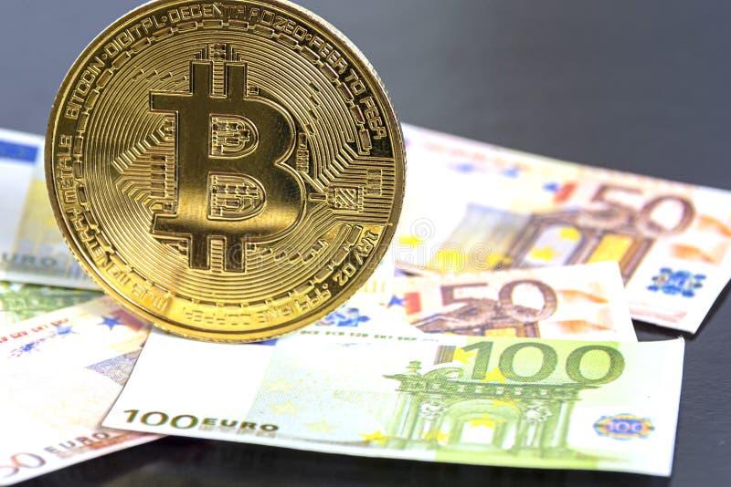Den nya virtuella valutan Golden Bitcoin i traditionell euro Eurosedlar som bakgrund Begrepp: gruvdrift och digitala valutor royaltyfria bilder