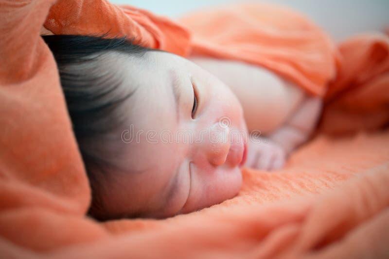 Den nyfödda asiatet behandla som ett barn flickan på säng royaltyfri bild