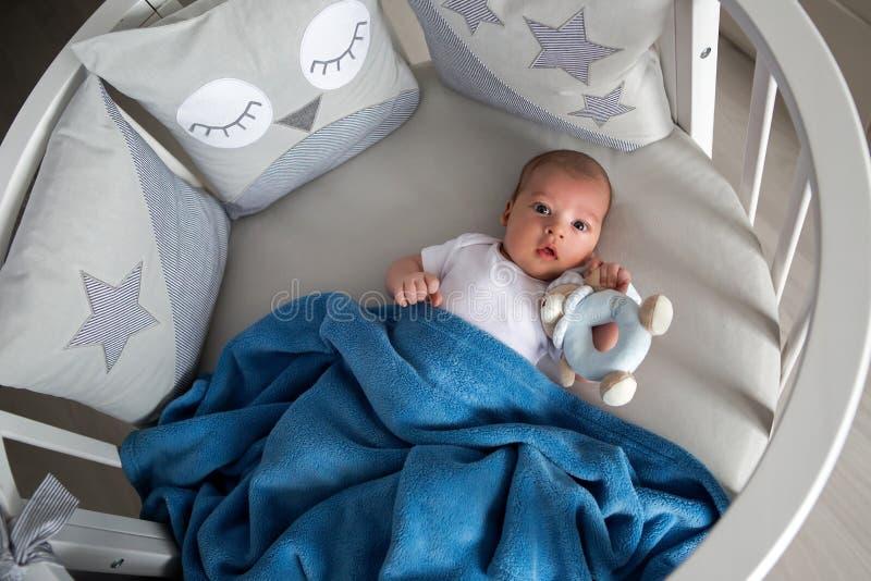 Den nyfödda pojken ligger i en rund säng royaltyfria bilder