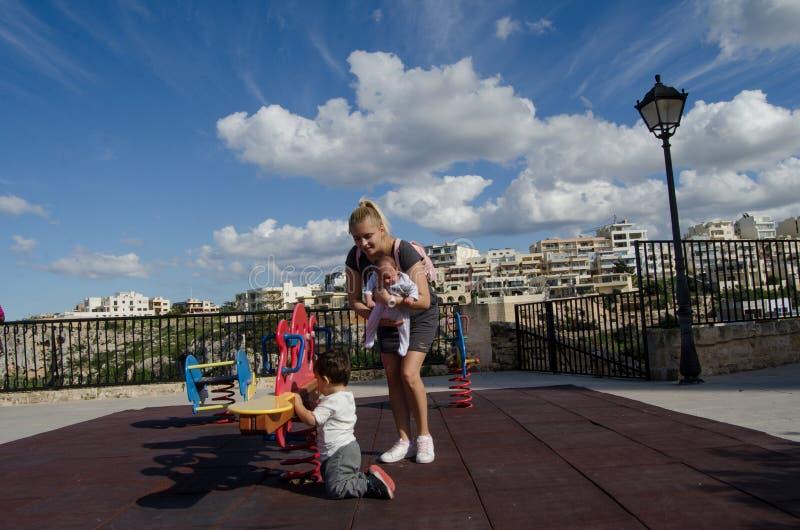 Den nyfödda unga blonda modern som rymmer, behandla som ett barn pojken, och spela med lilla barnet i barn parkera fotografering för bildbyråer