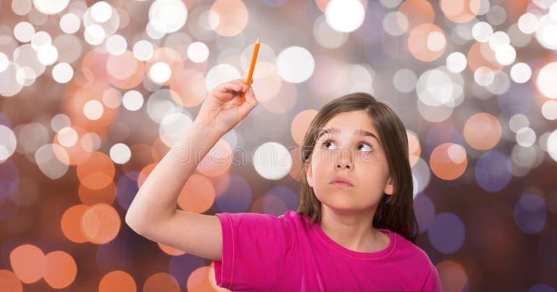 Den nyfikna flickan som ser upp, medan hållande, ritar över bokeh royaltyfri bild