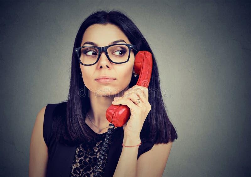 Den nyfikna kvinnan har ett intressant telefonsamtal arkivbilder