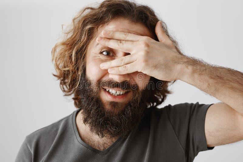 Den nyfikna mannen kan inte vänta för att se vad dig nederlaget Ståenden av den positiva snygga östliga grabben med skäggbeläggni fotografering för bildbyråer