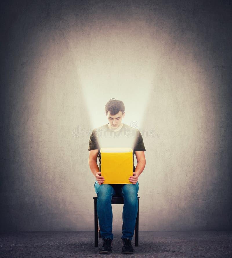 Den nyfikna mannen som sitter på en stol i ett mörkt rum som rymmer den gula asken på knä som inom ser som ett magiskt ljus, komm arkivfoton